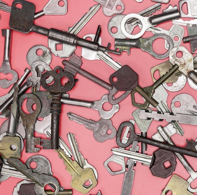 Sleutels die op roze achtergrond worden geplaatst