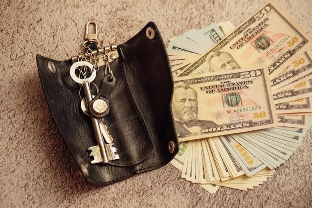 Sleutels en geld. dollars en appartementsleutels. dollars waarop de sleutels van het appartement zijn. het concept van het sparen en kopen van een appartement