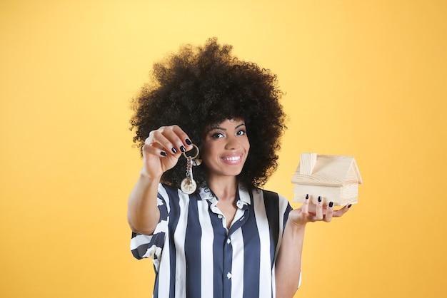 Sleutels en miniatuurhuis gepresenteerd door gemengde afro vrouwelijke makelaar op een gele achtergrond