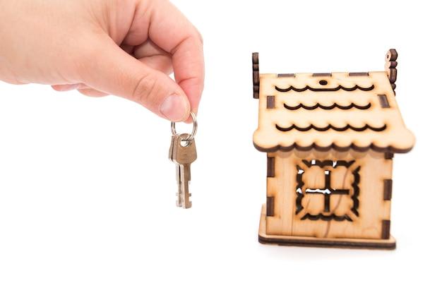 Sleutels in de hand en een houten huis op een witte achtergrond.