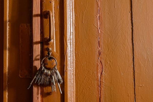 Sleutels in het slot van een oud deurconcept