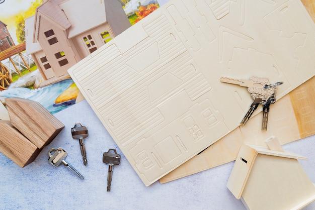 Sleutels over het papieren kaarthuis met houten huismodel