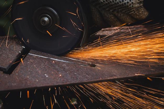 Slijpen snijden metalen plaat met haakse slijper machine en vonken, close-up.
