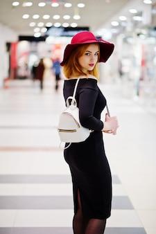 Slijtage van het manier de rode haired meisje op zwarte kleding en rode hoed met damesrugzak die bij handelswinkelcentrum wordt gesteld.