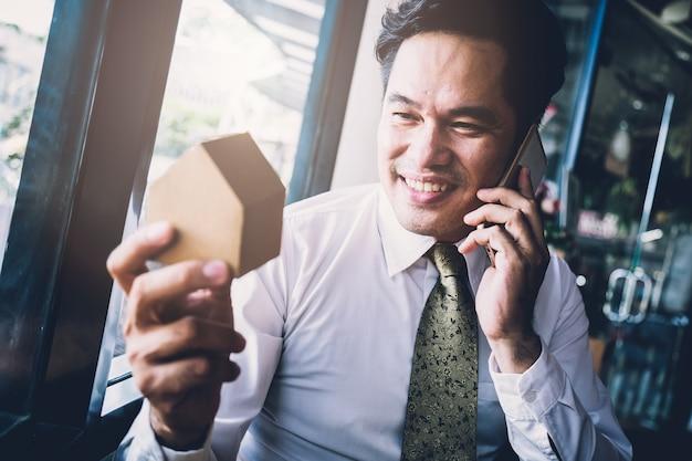 Slim aziatisch zakenmanhuisproject door smartphone in koffiewinkel