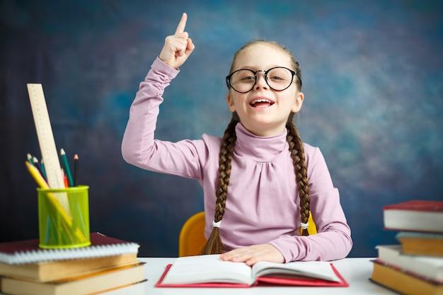 Slim elementair schoolmeisje dat huiswerk doet