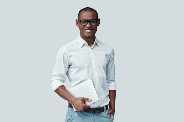 Slim en charmant. knappe jonge afrikaanse man die digitale tablet gebruikt en naar de camera kijkt terwijl hij tegen een grijze achtergrond staat