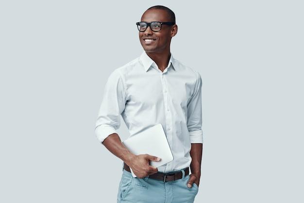 Slim en jong. knappe jonge afrikaanse man die digitale tablet gebruikt en glimlacht terwijl hij tegen een grijze achtergrond staat