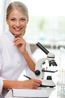 Slim en zelfverzekerd. glimlachende jonge vrouwelijke wetenschapper die in notitieblok schrijft en naar de camera kijkt terwijl ze op haar werkplek zit