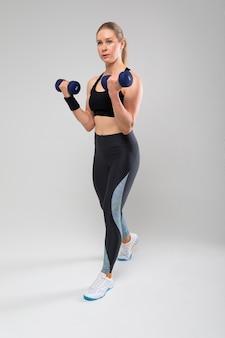 Slim fit blond meisje in een sport-uniform bezig met fysieke oefeningen