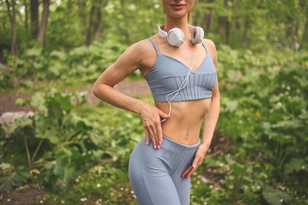 Slim fit meisje in blauwe sportkleding met grote witte koptelefoon sport en fitness in de zomer park buiten
