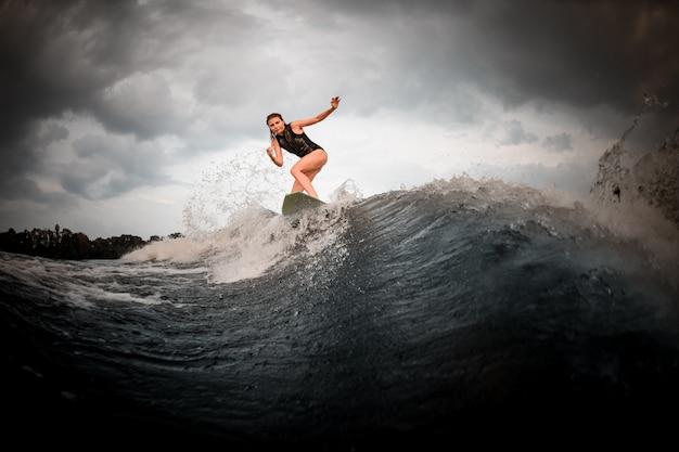 Slim fit meisje rijden op het wakeboard op de rivier op de achtergrond van bomen handen stijgen