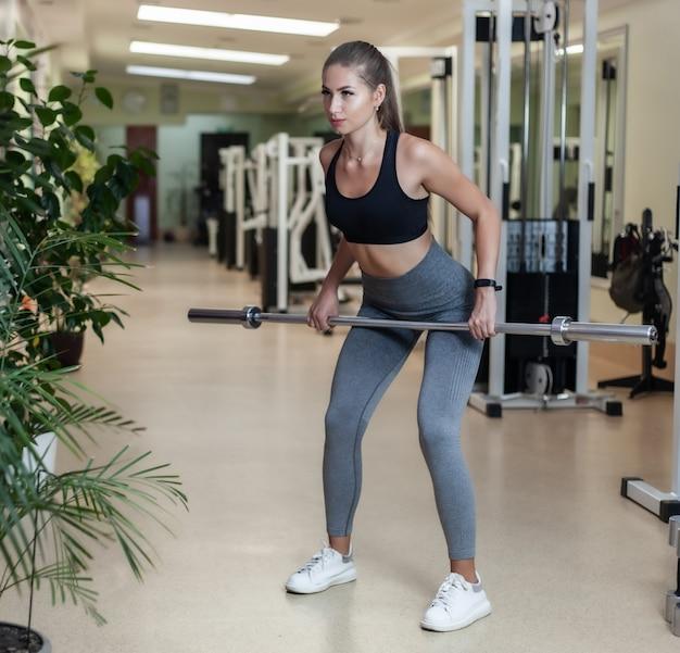 Slim fit vrouw in sportkleding doen een halter trekken op een helling in de sportschool kamer. gezonde levensstijl concept
