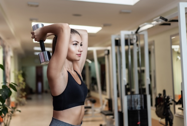 Slim fit vrouw in sportkleding extensie oefening achter het hoofd met halters in haar handen op de sportschool doet. gezonde levensstijl concept