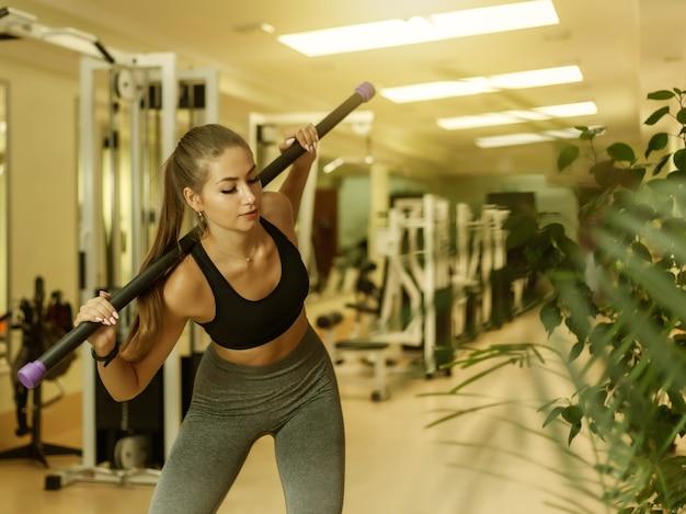 Slim fit vrouw in sportkleding gymnastische oefening doen met fitness stok op de schouders in de sportschool. gezond levensstijlconcept.