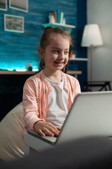 Slim glimlachend schoolkind dat bij literatuurhuiswerk werkt en educatieve informatie doorbladert