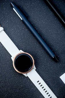 Slim horloge en slimme pen op zwarte achtergrond