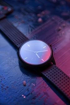 Slim horloge met analoog display en zwarte polsband op hitec hi tec computer moederbord. met 2 kleuren lampjes rood en blauw. detailopname