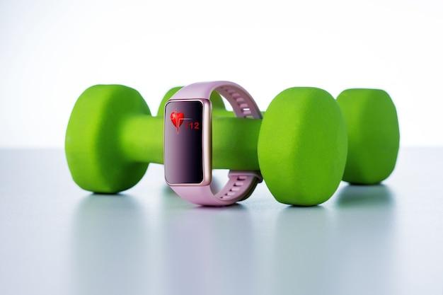 Slim horloge voor controle van hart, gezondheid met sportuitrusting op lichte achtergrond.