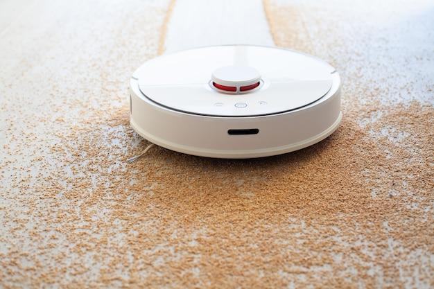 Slim huis. stofzuigerrobot draait op houten vloer in een woonkamer
