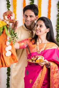 Slim indisch jong stel dat gudi padwa puja uitvoert in traditionele doeken & pooja thali. het is een hindoeïstisch nieuwjaar dat in heel india wordt gevierd