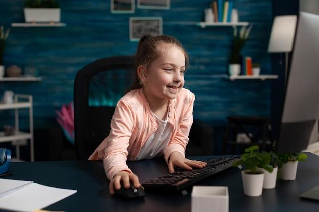 Slim klein schoolkind zittend aan bureau tafel met behulp van computer