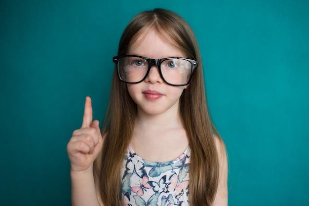 Slim meisje in glazen die op groene achtergrondonderwijs en schoolconcept richten