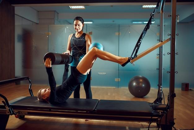 Slim meisje in sportkleding en instructeur, pilates training met bal op oefeningsmachine in sportschool.
