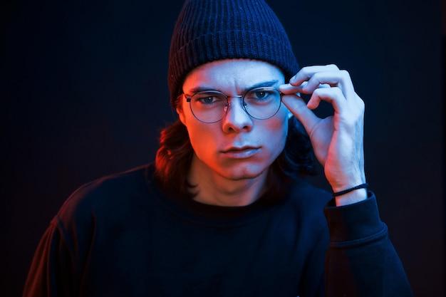 Slim persoon. studio opname in donkere studio met neonlicht. portret van ernstige man