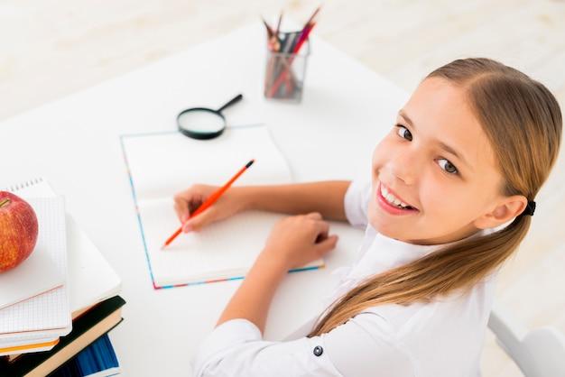 Slim schoolmeisje dat bij voorbeeldenboek schrijft