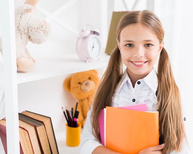 Slim schoolmeisje dat zich met voorbeeldenboeken bevindt
