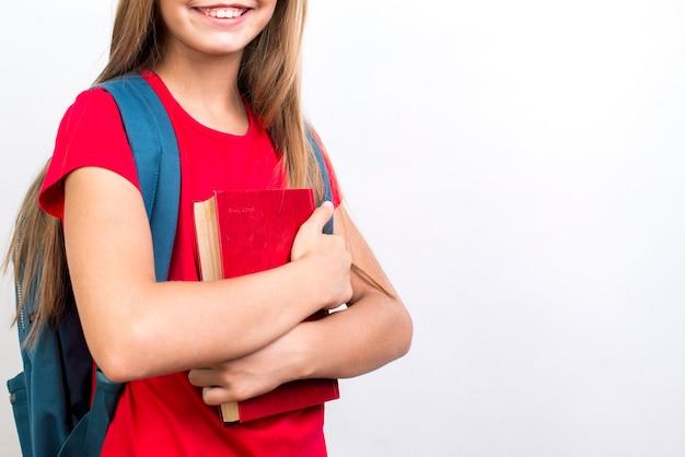 Slim schoolmeisje die handboek dragen