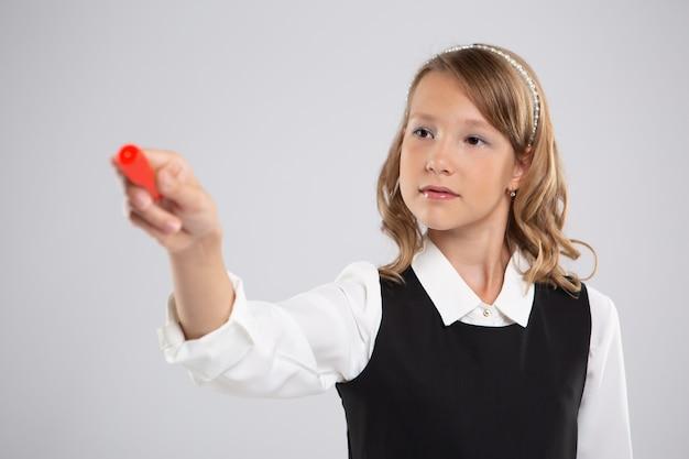 Slim schoolmeisje gaat met rood krijt schrijven