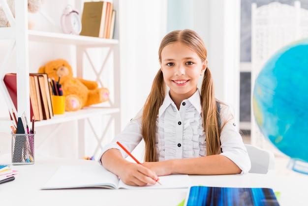 Slim schoolmeisje zit aan bureau