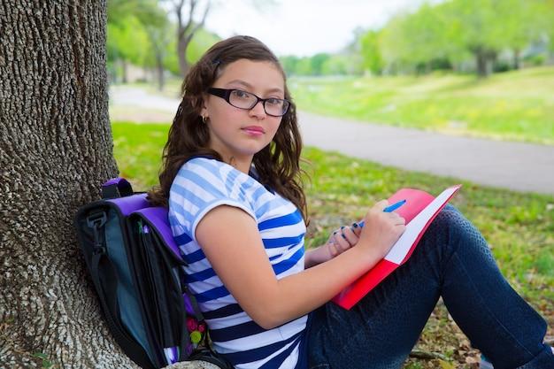 Slim studententienermeisje met schooltas onder parkboom