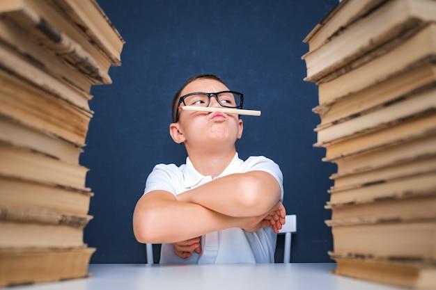 Slim uitziende jongen met potlood in zijn mond, wegkijken en denken
