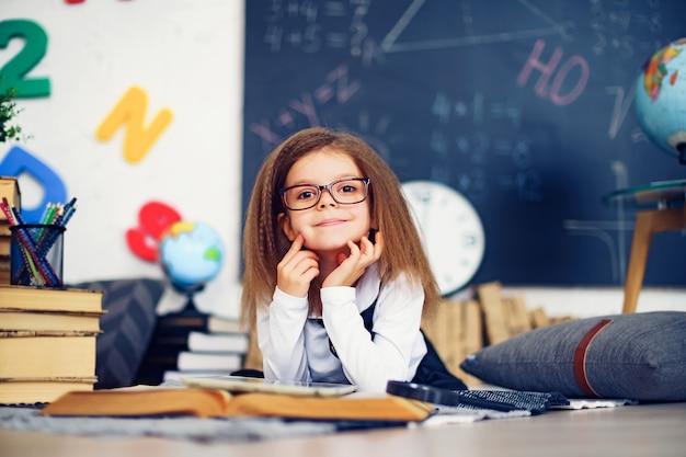 Slim weinig schoolmeisje met digitale tablet in een klaslokaal.