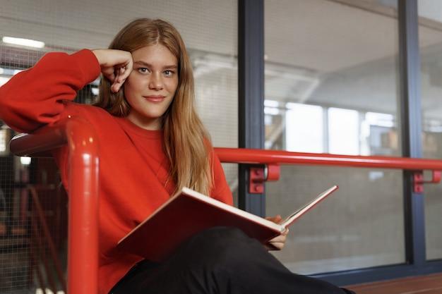 Slimme aantrekkelijke roodharige meisje, een tienerstudent die in bibliotheekzaal studeert, een boek leest.