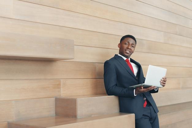 Slimme afrikaanse bedrijfsmens die laptop in bureau met behulp van