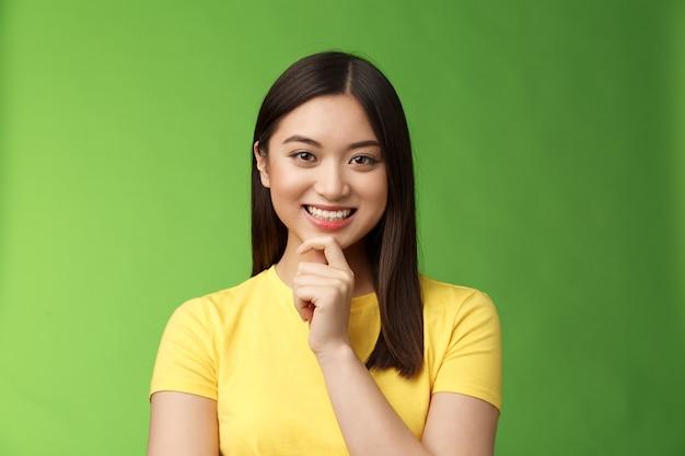 Slimme assertieve creatieve aziatische vrouwelijke student maakt interessante onderzoeksaannames, glimlacht geïntrigeerd en raakt kin attent, heeft een goed planidee, denkt na, overdenkt keuzes, groene achtergrond.