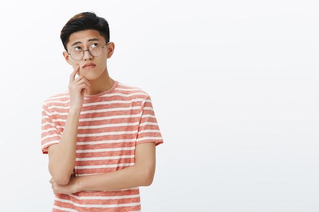 Slimme aziatische kerel lost puzzel in gedachten op en ziet er bedachtzaam en ontspannen uit in de rechterbovenhoek, denkt na, maakt aannames aan de wang terwijl hij een plan of beslissing maakt