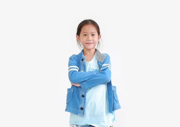 Slimme aziatische kindmeisje met gekruiste armen en blij gezicht