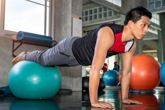 Slimme aziatische man in sportkleding training buikspieren met bal gym op fitness.