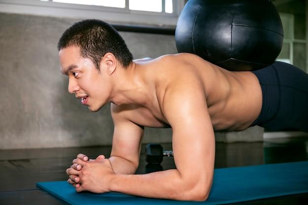 Slimme aziatische man in sportkleding training buikspieren met planking op fitness gym