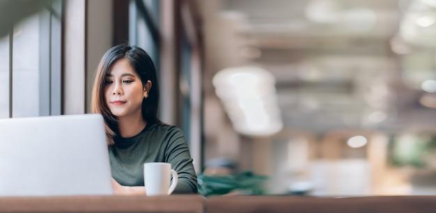 Slimme aziatische vrouw freelance online werken vanuit huis met laptop