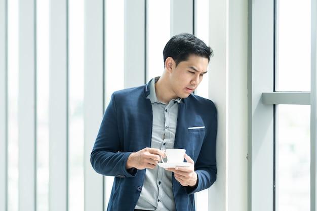 Slimme aziatische zakenman die en koffie in de ochtend bevinden zich dichtbij het venster in hoog de bouwbureau. het portret van de nadenkende zakenman met exemplaarruimte. ondernemers concept.