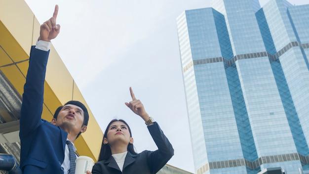 Slimme aziatische zakenmensen man en vrouw werknemer praten en vreugde samen in de situatie van kijken uit naar toekomstig idee