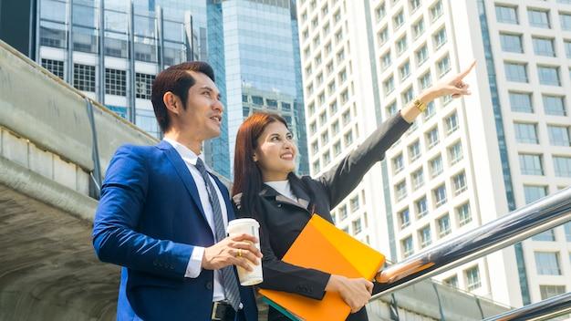 Slimme aziatische zakenmensen man en vrouw werknemer praten en vreugde samen in de situatie van vooruitkijken toekomstig idee