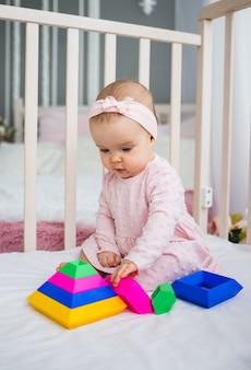 Slimme babymeisje verzamelt een piramide in de wieg in de kamer. ontwikkeling van het vroege kind
