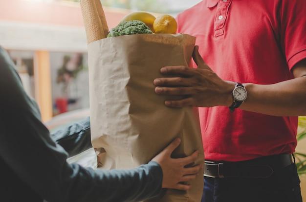 Slimme de leveringsman van de voedsellevering in rode eenvormig overhandigend vers voedsel aan ontvanger en jonge vrouwenklant die orde van koerier thuis ontvangen